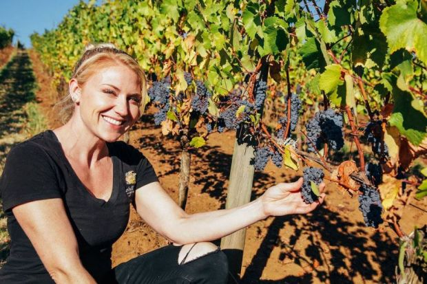 Smiling winemaker Ariel Eberle in the vineyard next to Pinot noir grape cluster.